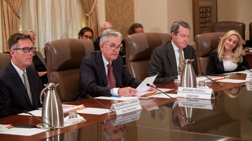 Members of the Federal Reserve Board of Governors, from left, Richard Clarida, Chairman Jerome H. Powell, Randal Quarles and Lael Brainard attend an open meeting on Oct. 31 in Washington.