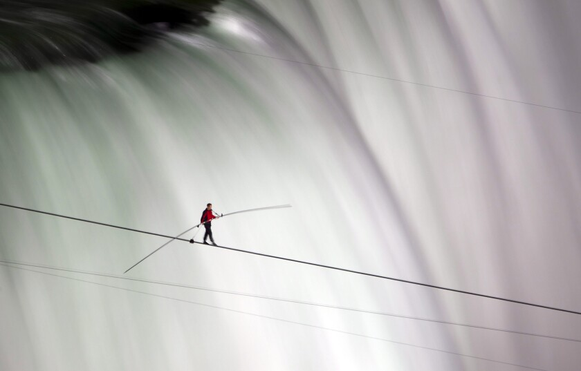 FILE - In this June 15, 2012 file photo, Nik Wallenda walks over Niagara Falls on a tightrope in Niagara Falls, Ontario. Wallenda, the great grandson of Karl Wallenda, is scheduled to help open a college's new health clinic next week by walking a wire over its Buffalo campus. The June 17, 2021 event will mark the opening of D'Youville College's Health Professions Hub. (AP Photo/The Canadian Press, Frank Gunn, File)