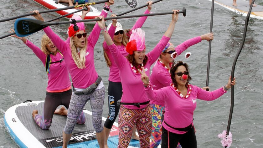 Team red celebrates after paddling around Newport Dunes for the Standup for the Cure, a stand-up pad