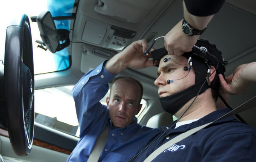Russ Martin of AAA is assisted by Joel Cooper, left, in hooking up the electroencephalographic-configured skull cap to the research vehicle during a demonstration in support of their new study on distracted driving.