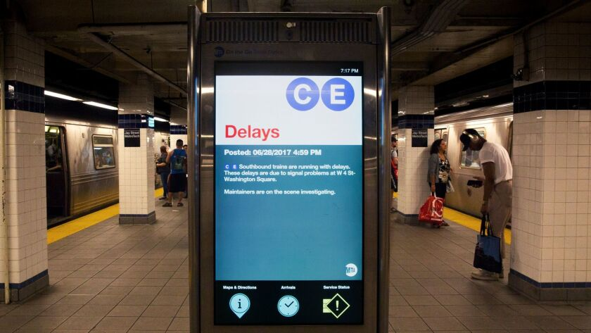 A sign warns of delays on the C and E trains due to signal problems.
