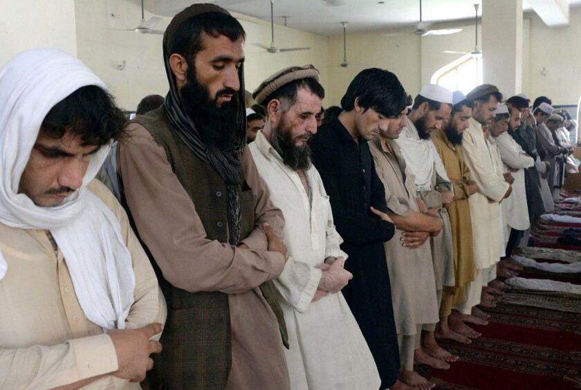 Afghan Muslims offer Friday prayers during the month of Ramadan on the outskirts of Jalalabad, the capital of Nangarhar province.