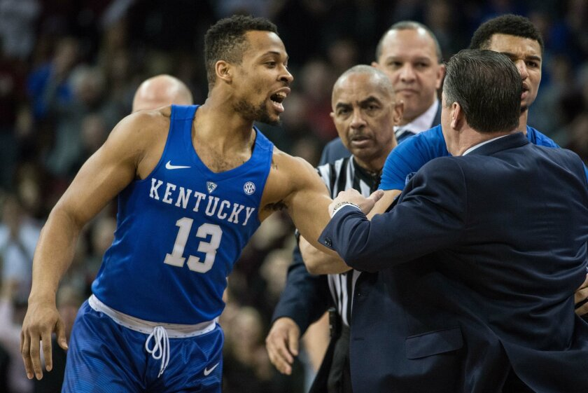 Kentucky guard Isaiah Briscoe (13) helps restrain head coach John Calipari as Calipari argued with the officials during the first half of an NCAA college basketball game against South Carolina, Saturday, Feb. 13, 2016, in Columbia, S.C. (AP Photo/Sean Rayford)