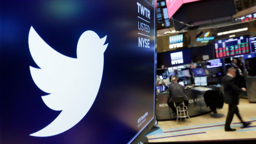 FILE - In this Feb. 8, 2018, file photo, the logo for Twitter is displayed above a trading post on t