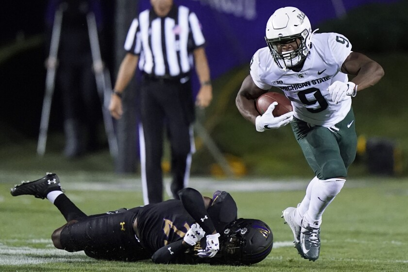Michigan State running back Kenneth Walker III runs past Northwestern defensive back Bryce Jackson on the way to a touchdown during the first half of an NCAA college football game in Evanston, Ill., Friday, Sept. 3, 2021. (AP Photo/Nam Y. Huh)