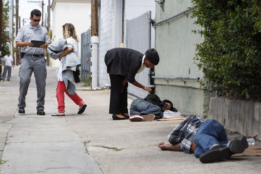 RAP paramedic Shawn Percival talks to a homeless woman as Lucky Michael, a homeless outreach coordinator for the Downtown San Diego Partnership, talks to Thomas Pappas, 63, after they found the woman, Pappas, and Robert Stevens, 61, foreground, sleeping
