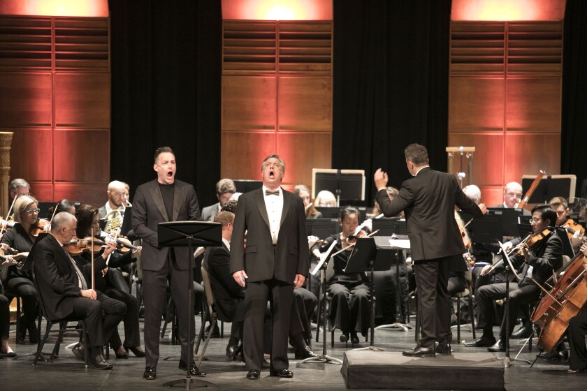 Tenor Stephen Costello, left, and baritone Stephen Powell perform a duet while conductor Bruce Stasyna leads the San Diego Symphony in a dual recital presented by San Diego Opera Wednesday night at the Balboa Theatre.