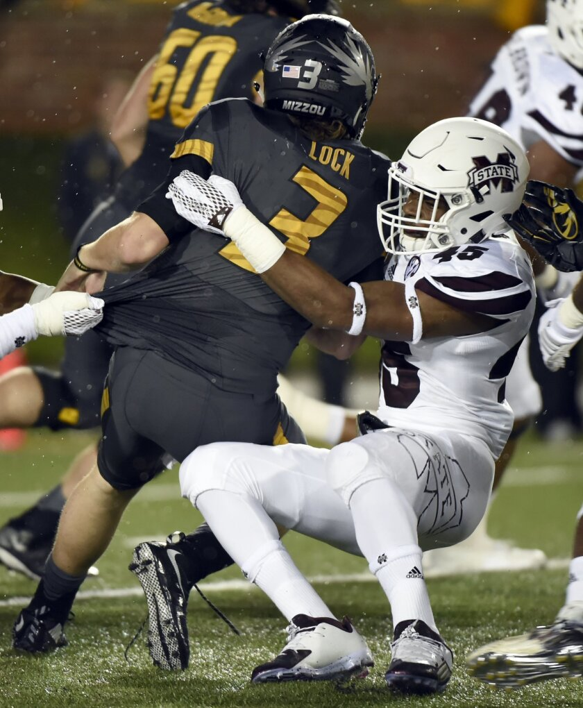 Missouri quarterback Drew Lock, left, is tackled by Mississippi State linebacker J.T. Gray during the first half of an NCAA college football game on Thursday, Nov. 5, 2015, in Columbia, Mo. (AP Photo/L.G Patterson)