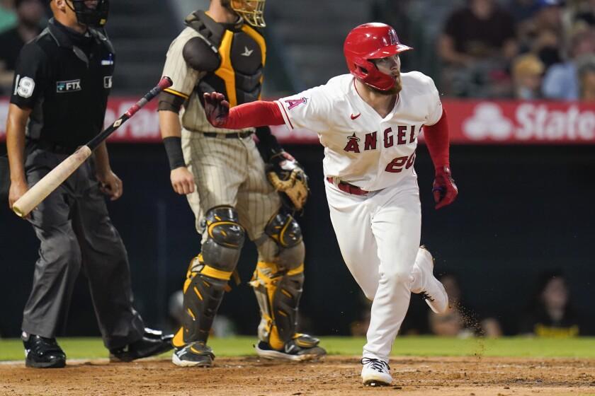El pelotero de los Angelinos de Los Ángeles Jared Walsh, a la derecha, observa su doble remolcador