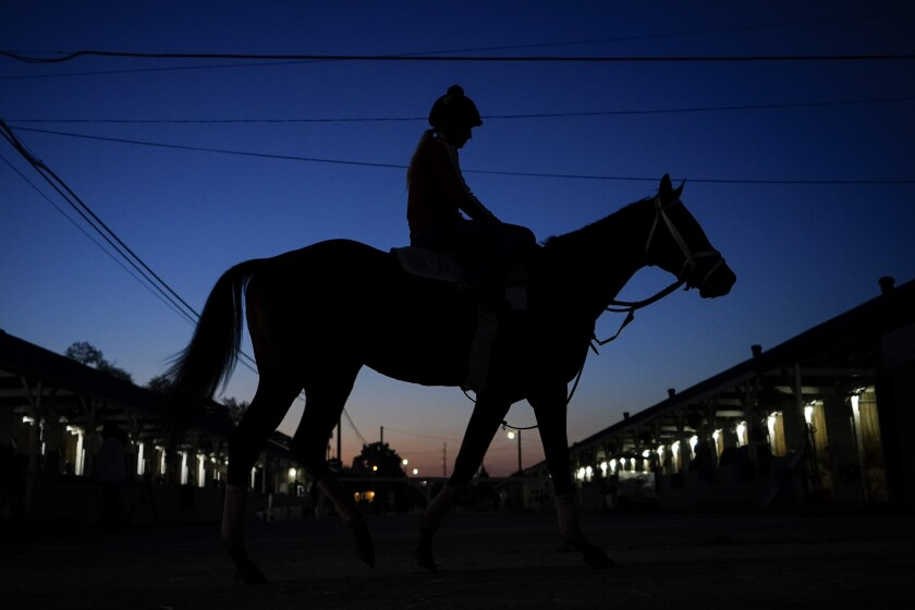 A jockey heads back to the barns at Churchill Downs Friday, April 30, 2021, in Louisville, Ky., a day before the 147th running of the Kentucky Derby. (AP Photo/Brynn Anderson)