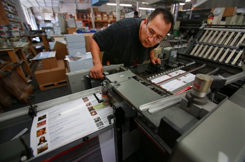 Jose Vazquez lines up brochures in a folding machine at Diego & Sons Printing.