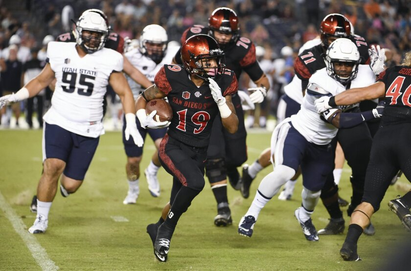 San Diego State running back Donnel Pumphrey (19) carries past the Utah State defense.