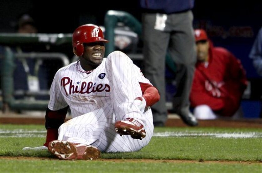 Philadelphia Phillies' Ryan Howard reacts after falling down injured on his way to first base as he makes the last out during the ninth inning of Game 5 of the National League division baseball series with the St. Louis Cardinals, Friday, Oct. 7, 2011, in Philadelphia. Cardinals won 1-0. (AP Photo/Alex Brandon)