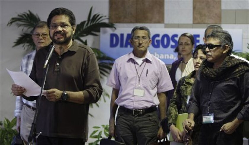 Ivan Marquez, left, chief negotiator for Colombia's Revolutionary Armed Forces of Colombia, or FARC, speaks to journalists at the continuation of peace talks with Colombia's government, as fellow FARC member Jesus Santrich, right, looks on in Havana, Cuba, Monday, Jan. 14, 2013. Colombia's main rebel group says it will end its unilateral cease-fire this weekend despite ongoing peace talks. The rebels' cease-fire ends Sunday. Marquez also outlined specific measures for agrarian reform, one of the main points of contention between the sides. (AP Photo/Franklin Reyes)