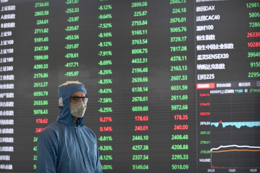 A worker stands near an electronic display board in the lobby of the Shanghai Stock Exchange building on Monday.