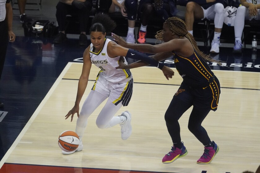 Dallas Wings' Satou Sabally (0) goes to the basket against Indiana Fever's Jantel Lavender (14) during the second half of a WNBA basketball game, Thursday, June 24, 2021, in Indianapolis. (AP Photo/Darron Cummings)
