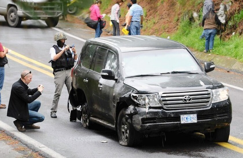 Investigators check a U.S. diplomatic vehicle attacked by Mexican federal police south of Mexico City. President Felipe Calderon had vowed to create a trustworthy force, but many are scoffing at that idea.