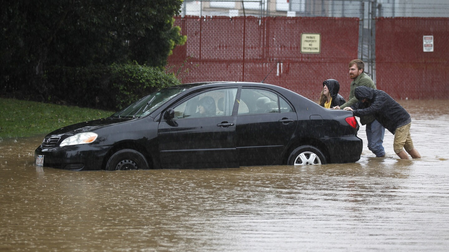 Sam Willette, left, Sean Cullen, and Andrew Oughton push the car of Erin Culllen (in driver's seat) on a flooded Roselle Street in Sorrento Valley during a rain storm in San Diego on Feb. 14, 2019. Erin had parked her car in the morning on the street near where she works only to return a few hours later to see the road flooded. After they pushed it to dry ground, they used buckets to remove the water and the car started. (Photo by K.C. Alfred/San Diego Union-Tribune)