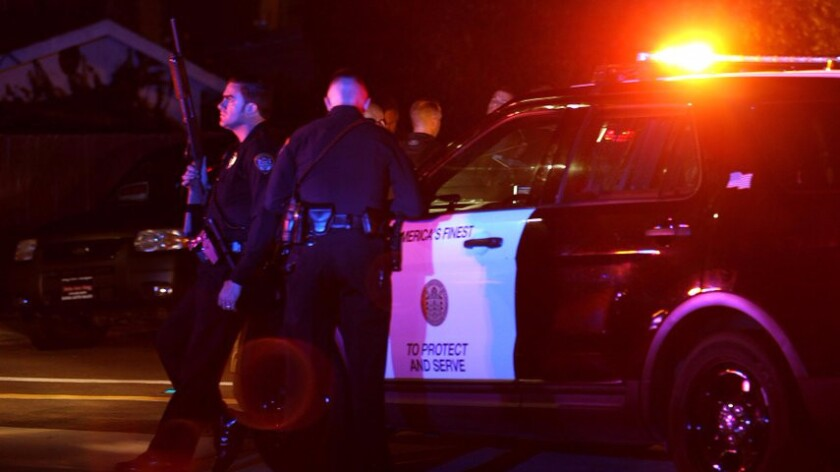 San Diego police and other law enforcement personnel gather near the scene of the shooting Thursday night.