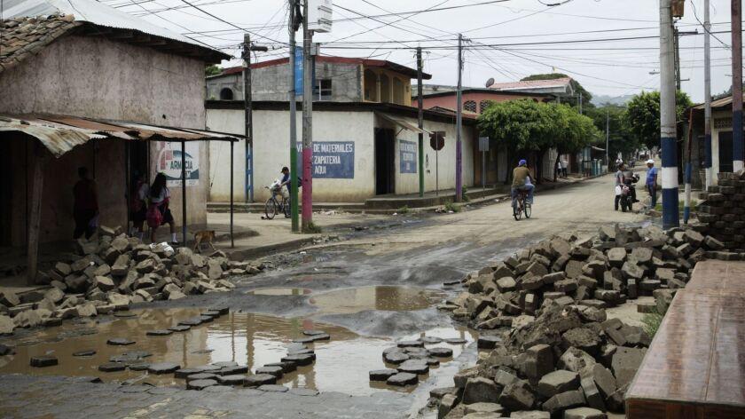 People past walk past a dismantled barricade in the Monimbo neighborhood of Masaya, Nicaragua, Thurs