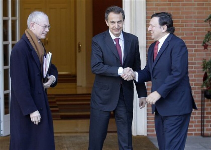 Spain's Prime Minister Jose Luis Rodriguez Zapatero, center, shakes hands with European Commission President Jose Manuel Durao Barroso, right, as EU president Herman Van Rompuy looks on at the Moncloa Palace in Madrid, before a meeting, Friday Jan. 8, 2010. (AP Photo/Paul White)