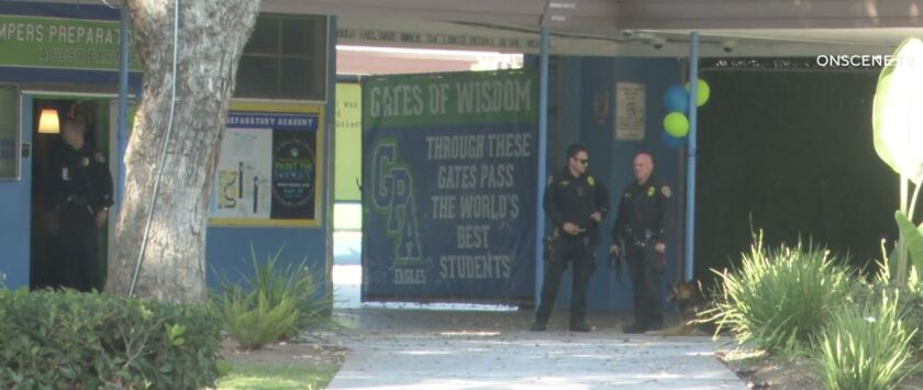 San Diego police officers, including a dog handler, stand on the campus of Gompers Preparatory Academy after a bomb threat was phoned into the school Monday. No threat was found.