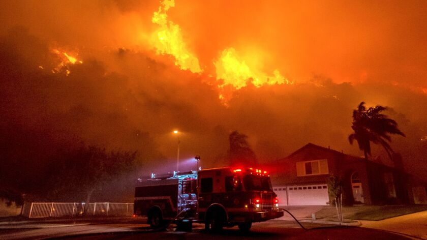 In this Monday, Sept. 25, 2017 photo, firefighters battle to save homes as a blaze continues to burn