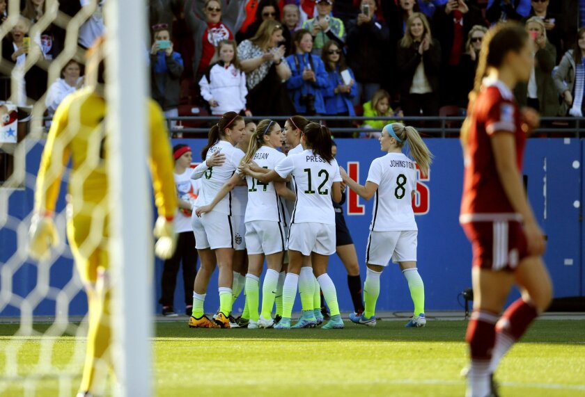 The United States' Morgan Brian (14), Christen Press (12) and Julie Johnston (8) celebrate with the rest of the team after Carli Lloyd scored against Mexico in the second half of a CONCACAF Olympic qualifying tournament soccer match, Saturday, Feb. 13, 2016, in Frisco, Texas. (AP Photo/Tony Gutierr