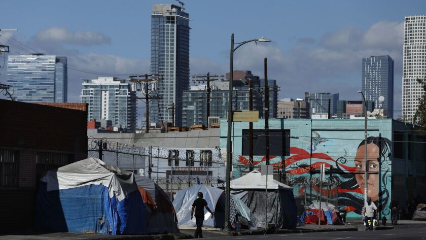 People walk past a homeless encampment on 6th St., just west of Central Ave. in downtown Los Angeles on Oct. 11.