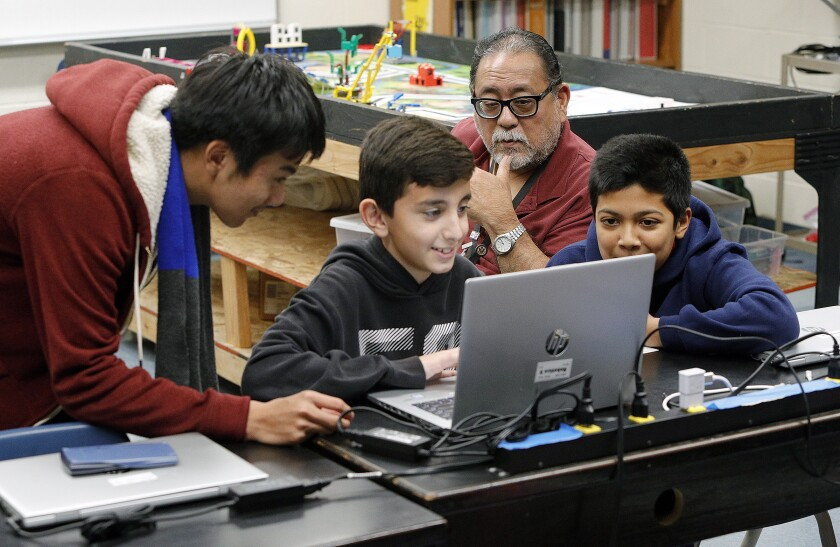 Robotics instructor Randy Kamiya watches students John Nguyen, 13, Avakeem Avakian, 11, and Ibrahim Ahmad, 13, work with a Lego robotics program during a class at Roosevelt Middle School on Monday.