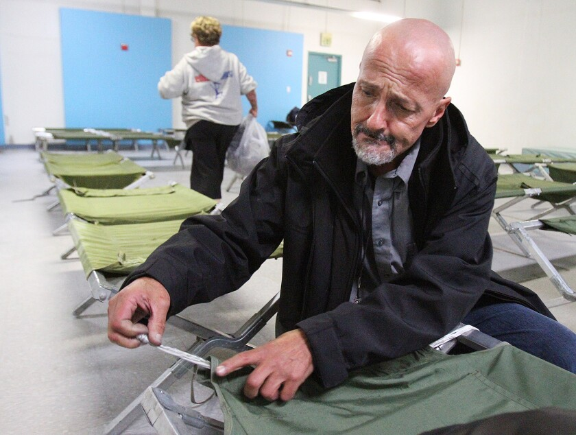 """Arthur Morris, who has been homeless about one year, pulls a small rope through the canvas of his cot to create a better sleeping surface at Ascencia in Glendale for the Glendale Winter Shelter Program on Monday, December 2, 2013. He does this because the metal bars that used to be there were once used as a weapon and have since been removed from all the cots making them a little short, and difficult to contain a pillow. Morris' comment was, """"Don't complain about it. Figure out a way to solve it,"""" which is why he came up with this solution to his cot, which other people in the room thought was pretty smart. The shelter opened last night for a handful of people, but the 80 bed capacity is expected to fill if it rains in the next couple days. (Tim Berger/Staff Photographer)"""