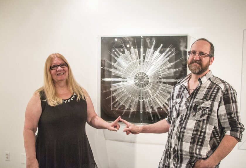 Curators Debby and Larry Kline with Cheryl Nickel's 'Meditation on Science,' a mandala made of chemistry-lab pipettes