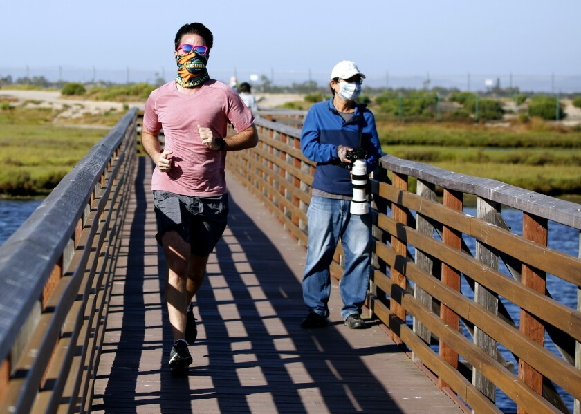 A jogger and a wildlife photographer wear masks at Bolsa Chica Ecological Reserve in Huntington Beach on Wednesday.