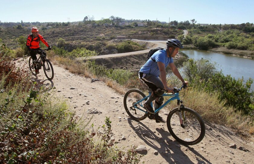Mountain bikers Cristian Bustamante (right) and David Gonzalez ride on a trail above Lake Calavera in Carlsbad on Thursday.