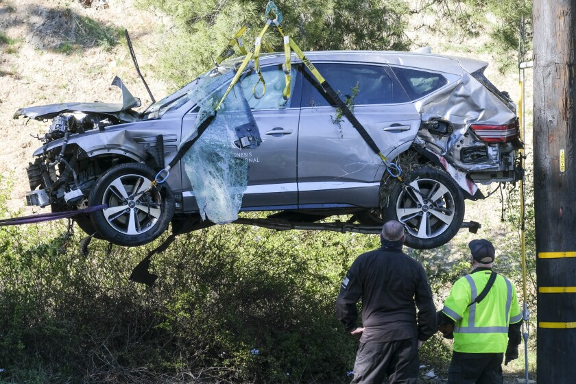 FILE - In this Feb. 23, 2021, file photo, a crane is used to lift a vehicle following a rollover accident involving golfer Tiger Woods, in the Rancho Palos Verdes suburb of Los Angeles. The Los Angeles County sheriff plans to announce Wednesday, April 7, 2021, what caused Woods to crash an SUV in Southern California earlier in the year, seriously injuring himself in the wreck. (AP Photo/Ringo H.W. Chiu, File)