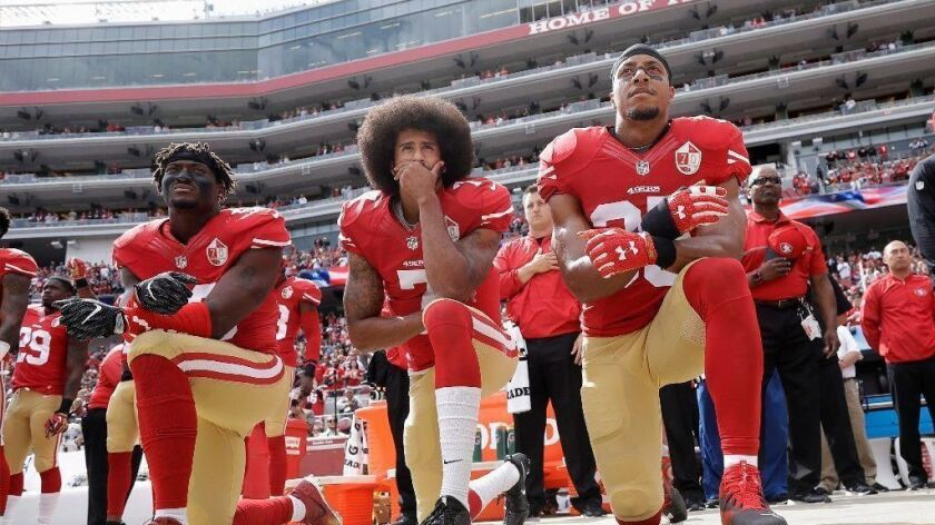 Former San Francisco 49ers quarterback Colin Kaepernick kneels before a 2016 game, flanked by teammates Eli Harold and Eric Reid, as a protest against police brutality.
