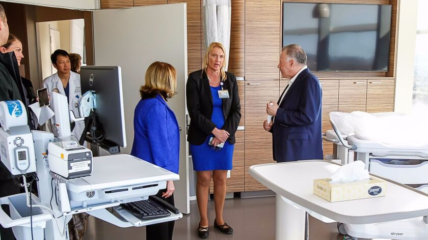 Patty Maysent, CEO of UC San Diego Health, gives a tour of Jacobs Medical Center to donors Mary (left) and Gary (right) West on Nov. 9, 2016.
