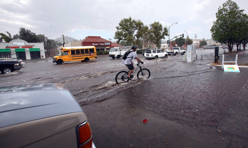 A bicyclist rides through the puddle near the corner of Kenwood Drive and Campo Road in Casa de Oro.