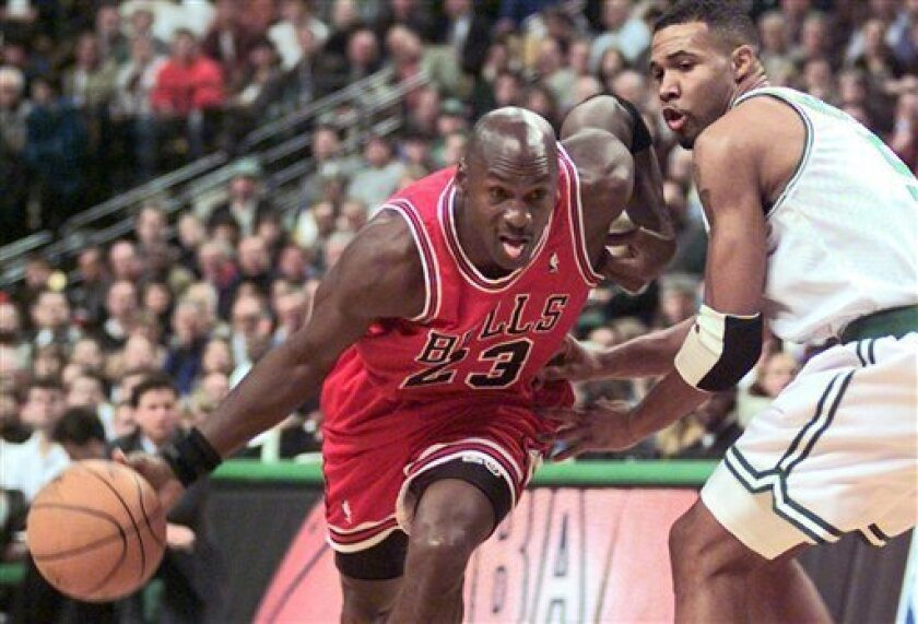 FILE - In this Oct. 31, 1997, file photo Chicago Bulls guard Michael Jordan (23) drives past Boston Celtics Ron Mercer (5) during an NBA basketball game in Boston.  A Bismarck, N.D., man who used to own McDonald's restaurants is about $10,000 richer after selling a 20-year-old container of McJordan