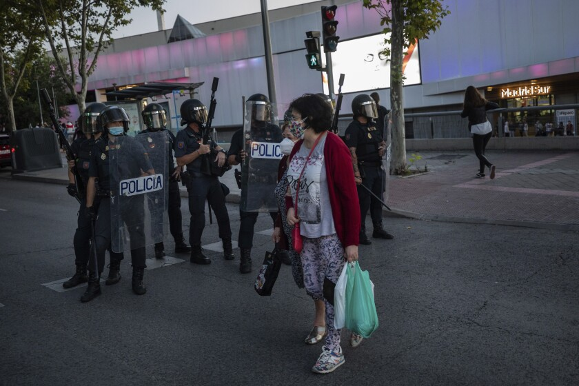 Two neighbours of restricted mobility areas in Madrid due to the coronavirus outbreak cross the street in front an anti-riot police unit short after a residents protest demanding more resources for public health system and against social inequality in the southern neighbourhood of Vallecas, Madrid, Spain, Thursday, Sept. 24, 2020. The regional government is set to announce Friday new restrictions in Madrid, where gatherings are limited to a maximum of 6 people and more than 850,000 residents have been partially locked down this week. (AP Photo/Bernat Armangue)