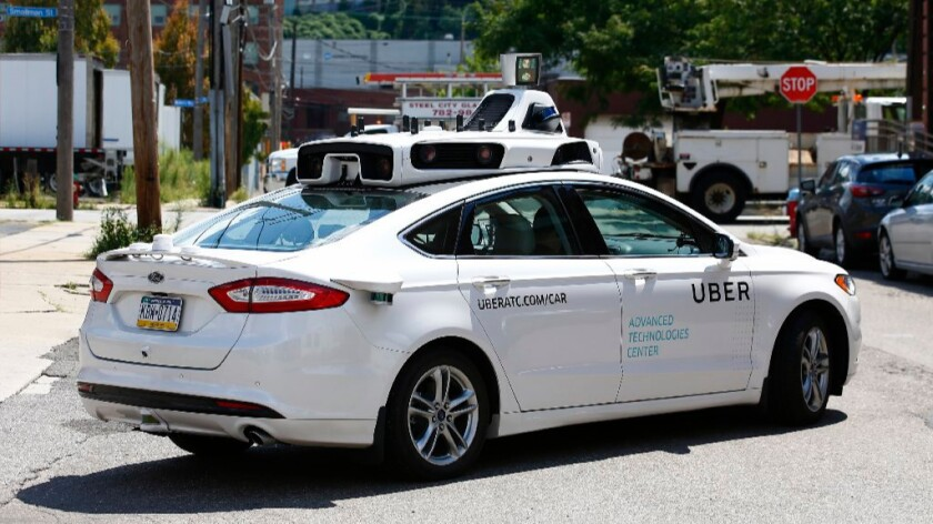 A self-driving Ford Fusion hybrid car is test-driven in Pittsburgh. Uber said that passengers in Pittsburgh will be able to summon rides in self-driving cars with the touch of a smartphone button.