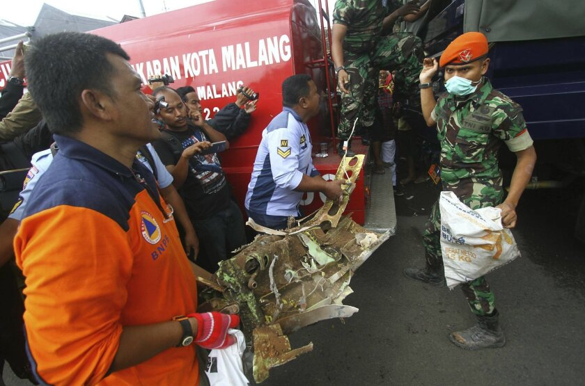 Rescuers carry a part of Indonesian Air Force plane which crashed into a house in Malang, East Java, Indonesia, Wednesday, Feb. 10, 2016. The Brazilian-made Embraer EMB 314 Super Tucano plane crashed during a routine training flight. (AP Photo)