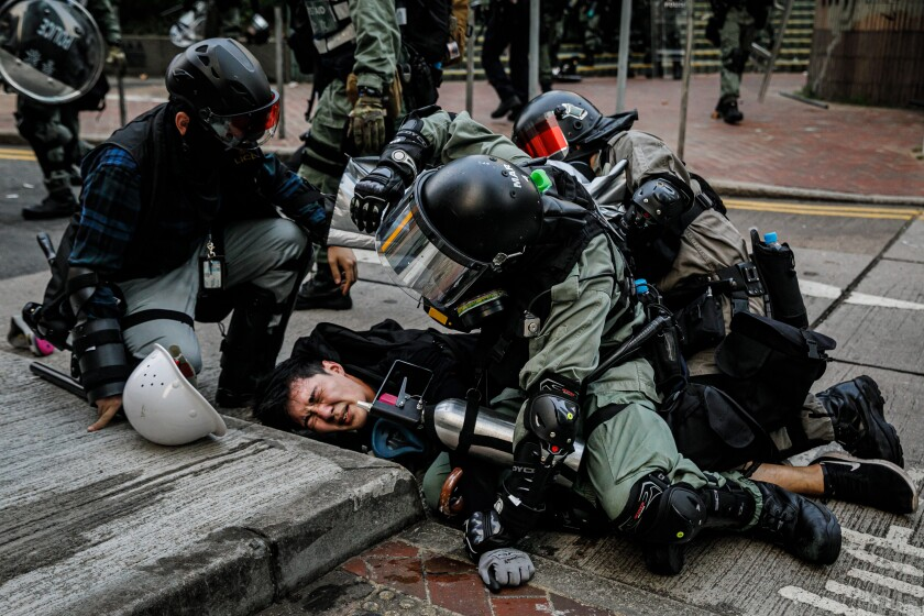 HONG KONG, CHINA -- SUNDAY, SEPTEMBER 29, 2019: Police officers in riot gear pin down a young protester as they confront demonstrators with tear gas, batons and shields and make mass arrests near the HK Police Headquarters as chaos grips the city leading up to ChinaÕs National Day this week, in Hong Kong, on Sept. 29, 2019. Despite Chief Executive Carrie LamÕs bowing to the demonstratorsÕ key demand Ð withdrawal of a controversial extradition bill, pro-democracy demonstrators are now calling for Lam to immediately meet the rest of their demands. This includes an independent inquiry into policeÕs use of force, amnesty for those arrested, a halt on the use of the word ÒRiotÓ when describing the rallies, and lastly, calls for universal suffrage for the people of Hong Kong. (Marcus Yam / Los Angeles Times)