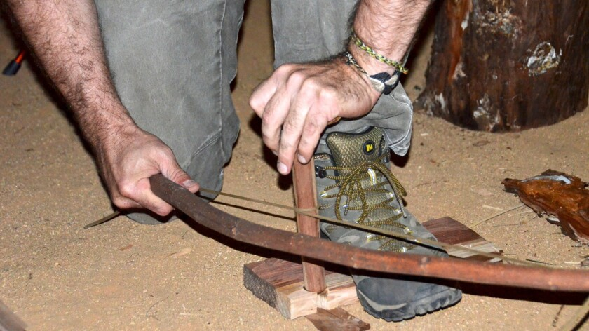 Bo Glover demonstrates how to start a fire using a make-shift bow during the Primitive Skills Socie