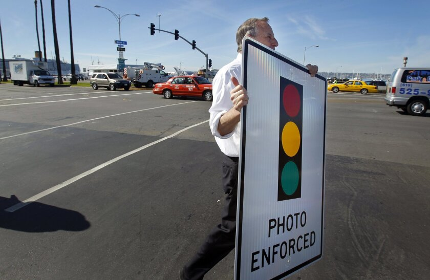 Mayor Bob Filner hauls off a red-light camera warning sign, no longer needed after his announcement that the city was doing away with the cameras citywide.