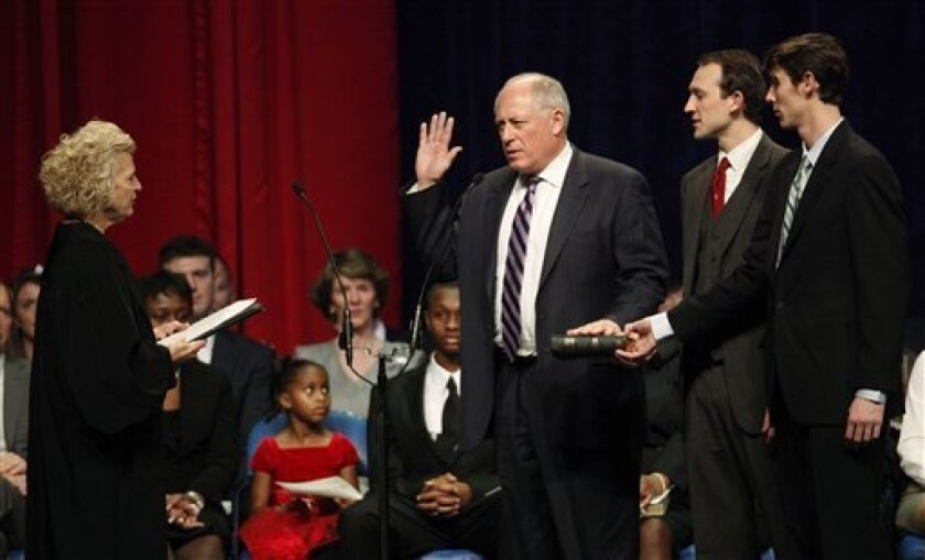 Illinois Gov.Pat Quinn, center, takes the oath of office of governor, from Illinois Supreme Court Justice Anne M. Burke, as Quinn's sons Patrick and David watch during inaugural ceremonies Monday, Jan. 10, 2011 in Chicago. (AP Photo/Charles Rex Arbogast)