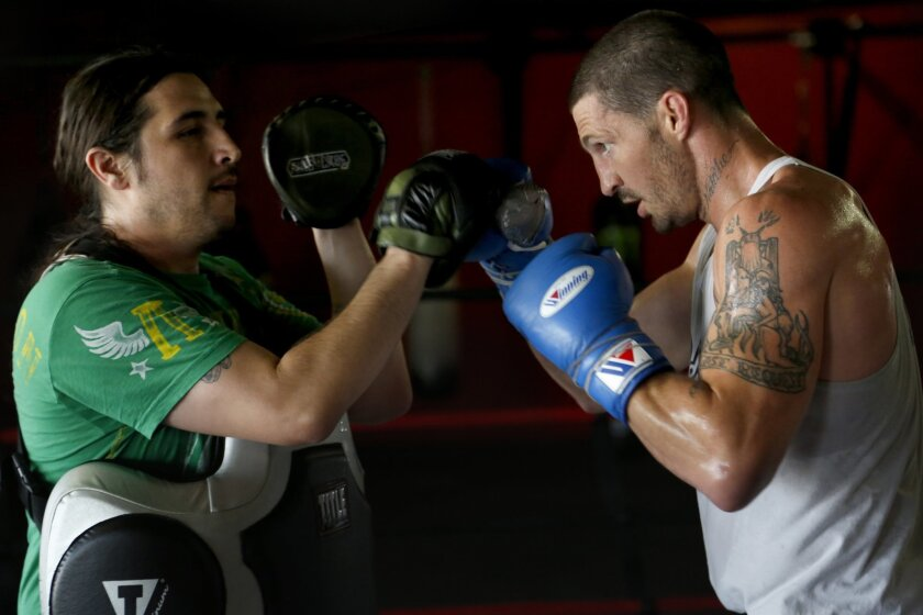 Alliance MMA fighter Erin Beach (right) trains with coach Adrian Melendrez at Alliance Training Center.
