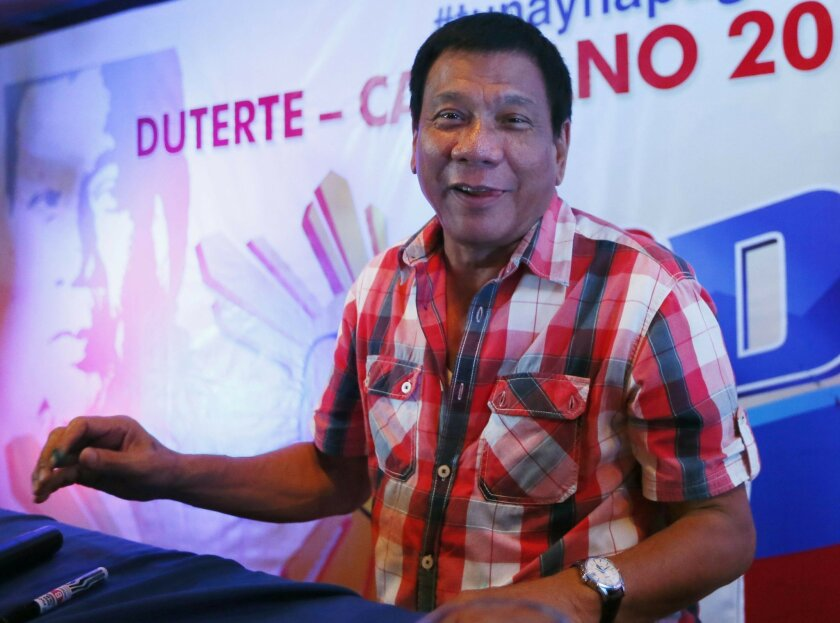 In this Monday, May 9, 2016 photo, front-running presidential candidate Mayor Rodrigo Duterte smiles during a news conference shortly after voting in a polling precinct at Daniel R. Aguinaldo National High School, Matina district, his hometown in Davao city in southern Philippines. Philippine lawmakers say Rodrigo Duterte has been elected president and Leni Robredo elected vice president in official vote count.(AP Photo/Bullit Marquez)