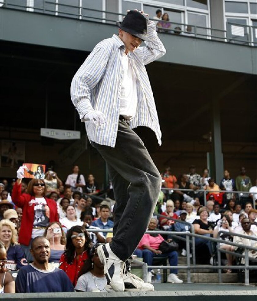 """Tim Gilleand 30, of South Bend, Ind., does the """"moon walk"""" on top of the baseball dugout during the memorial for Michael Jackson at the Steel Yard Stadium in Gary, Ind., Friday, July 10, 2009. Thousands of Michael Jackson fans flocked Friday to the city where he spent the first 11 years of his life"""