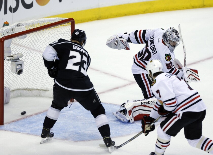Kings captain Dustin Brown, left, scores past Chicago Blackhawks goalie Corey Crawford and defenseman Brent Seabrook during Game 4 of the Western Conference finals at Staples Center.